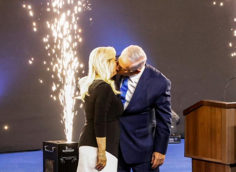 Israeli Prime Minister Benjamin Netanyahu kisses his wife Sara on election night, celebrating a victory that puts him on a path to become the country's longest-serving prime minister