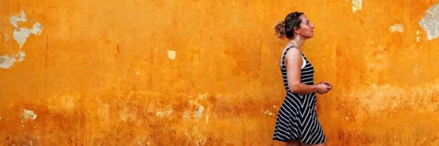 A woman walking in front of a wall