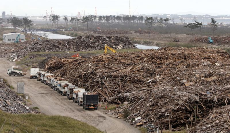 In this Oct. 10, 2012 photo, a yellow crane is seen in the heap of the sorted out rubble of the March 11, 2011 earthquake and tsunami, at the rubble collection site near the Arahama beach in Sendai, northeastern Japan. Japan's accounting of its budget for reconstruction from the disasters is crammed with spending on unrelated projects, while all along Japan's northeastern coast, dozens of communities remain uncertain of whether, when and how they will rebuild. (AP Photo/Koji Sasahara)