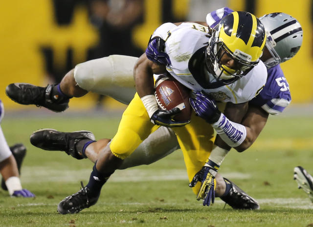 Michigan wide receiver Dennis Norfleet, front, is tackled by Kansas State linebacker Blake Slaughter during the first half of the Buffalo Wild Wings Bowl NCAA college football game on Saturday, Dec. 28, 2013, in Tempe, Ariz. (AP Photo/Matt York)