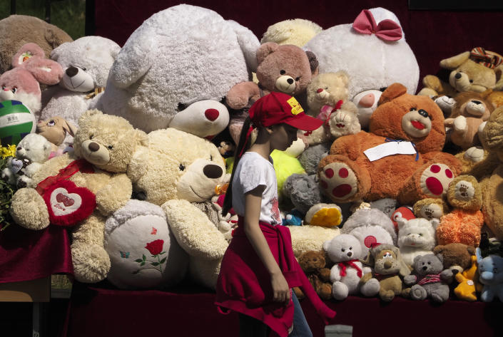 A girl walks past toys brought by people near a school after a shooting on Tuesday in Kazan, Russia, Thursday, May 13, 2021. Russian officials say a gunman attacked a school in the city of Kazan and Russian officials say several people have been killed. Officials said the dead in Tuesday's shooting include students, a teacher and a school worker. Authorities also say over 20 others have been hospitalised with wounds. (AP Photo/Dmitri Lovetsky)