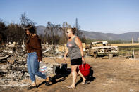 Kimberly Price and granddaughter Kyra Cedillos, 14, walk among burned homes in the Greenville community of Plumas County, Calif., on Sunday, Sept. 5, 2021, while feeding cats left behind by Dixie Fire evacuees. (AP Photo/Noah Berger)