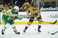 Minnesota Wild left wing Kevin Fiala (22) and Vegas Golden Knights defenseman Shea Theodore (27) vie for the puck during the first period of an NHL hockey game Wednesday, March 3, 2021, in Las Vegas. (AP Photo/John Locher)