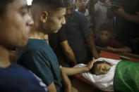 Relatives of Palestinian Omar al-Nile, 12, who was shot on Saturday during a violent demonstration on the eastern border between Gaza and Israel, mourn over his body during his funeral in Gaza City, Saturday, Aug. 28, 2021. (AP Photo/Khalil Hamra)