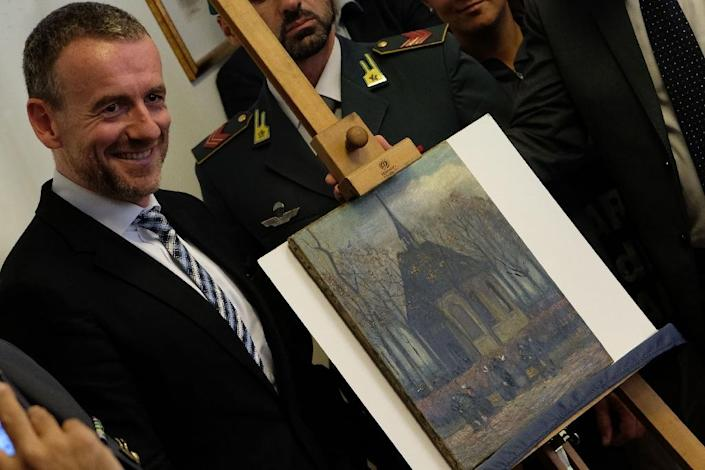 """Axel Ruger, Director of the Van Gogh museum poses next to """"Congregation Leaving the Reformed Church in Nuenen"""" by Vincent van Gogh, one of the two Van Gogh paintings stolen in Amsterdam 14 years ago and recently recovered by organised crime in Italy (AFP Photo/Mario Laporta)"""