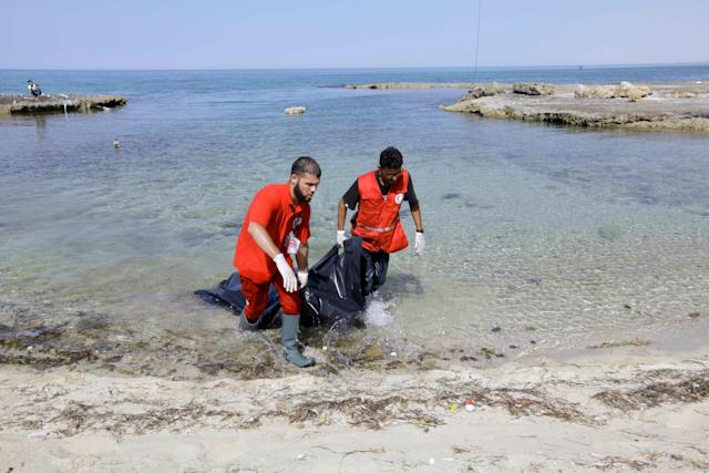 Rescuers carry a bag containing the body of a migrant at the coast of Tajoura, east of Tripoli, Libya, on June 27.