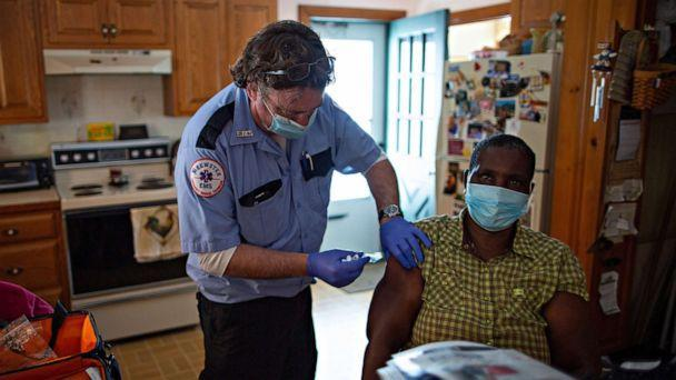 Paramedic Rob Barss administers the J & J COVID-19 vaccine to Mary Wanjiku,a health care aid to a Leominster home-bound resident, as part of the pilot mobile vaccine distribution program called, Last Mile Vaccine Delivery,in Leominster, Mass. (CJ Gunther/EPA via Shutterstock)