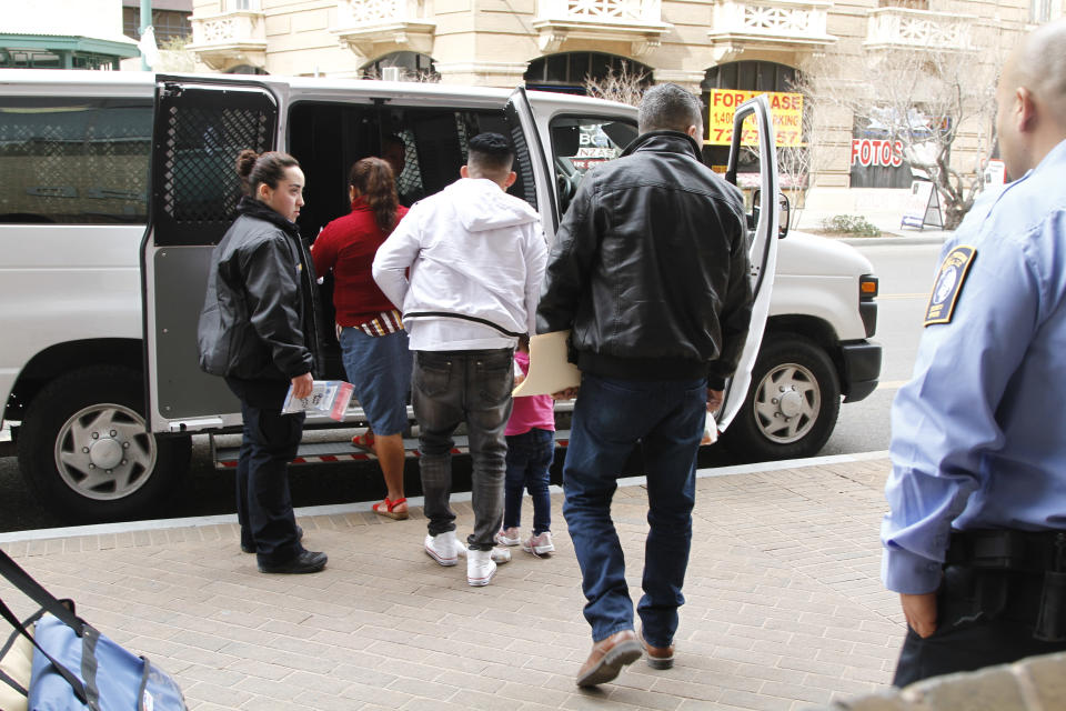 FILE - In this Feb. 28, 2020, file photo, Immigration detention guards flank a father, in white, holds the hand of his daughter as they and other asylum seekers leave court under guard after some of them learned that they won't have to return to Mexico in light of a major federal court ruling against the Trump administration in El Paso, Texas. Attorney General Merrick Garland has tossed out a Trump administration policy that barred immigration judges from temporarily shelving some deportation cases. Garland on Thursday, July 15, 2021, overruled a decision by then-Attorney General Jeff Sessions that judges couldn't put those cases on hold. (AP Photo/Cedar Attanasio, File)