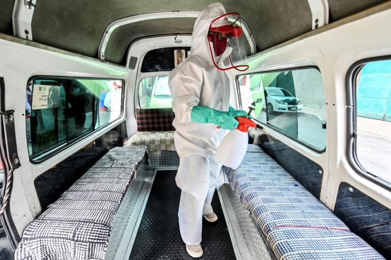 A cleaning worker wearing personal protective equipment disinfects a public tranport van in Mexico City, on July 30, 2020