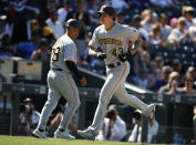 Pittsburgh Pirates third base coach Joey Cora , back, congratulates Steven Brault as he circles the bases after hitting a solo home urn off Colorado Rockies relief pitcher Jesus Tinoco in the seventh inning of a baseball game Sunday, Sept. 1, 2019, in Denver. (AP Photo/David Zalubowski)