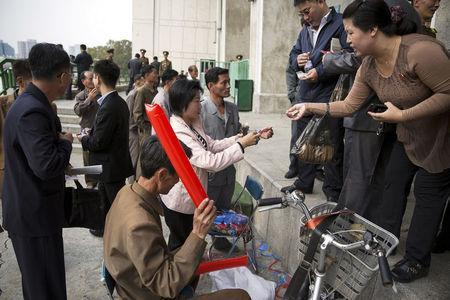 FILE PHOTO: People use North Korean won and U.S. dollars to buy inflatable clappers at a black market exchange rate before a football match at the Kim Il Sung Stadium in Pyongyang October 8, 2015. REUTERS/Damir Sagolj/File Photo