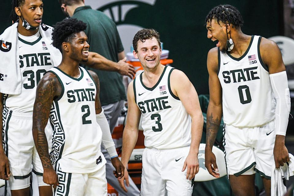 For left, Michigan State's Rocket Watts, Foster Loyer and Aaron Henry joke around on the bench late during the second half of the game against  Eastern Michigan on Wednesday, Nov. 25, 2020, at the Breslin Center in East Lansing.
