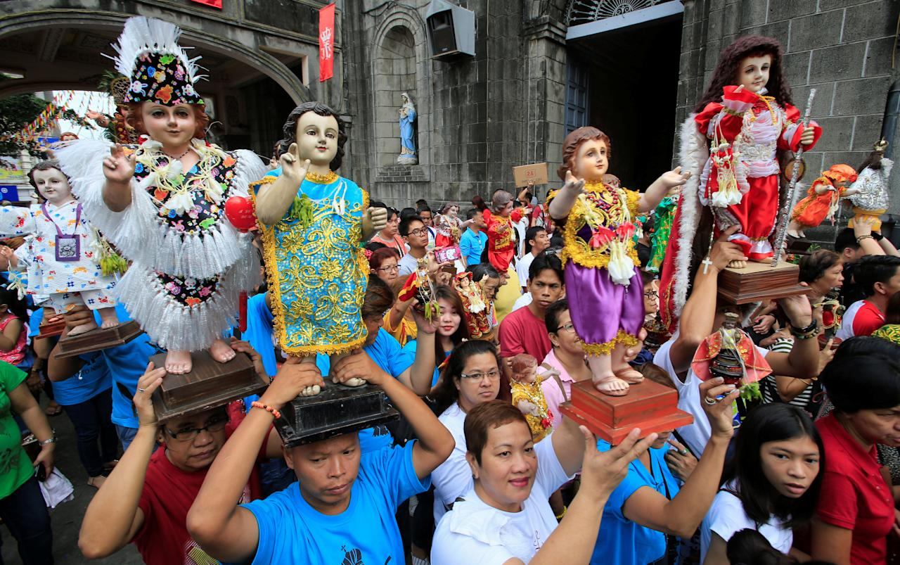 Devotees parade different figurines of Santo Nino (infant Jesus) during a procession in Tondo city, Metro Manila, Philippines January 20, 2018, a day before the annual feast day of Santo Nino on Sunday. REUTERS/Romeo Ranoco