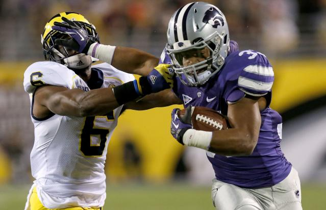 Kansas State's John Hubert, right, stiff-arms Michigan's Raymon Taylor (6) while running with the ball during the first half of the Buffalo Wild Wings Bowl NCAA college football game on Saturday, Dec. 28, 2013, in Tempe, Ariz. (AP Photo/Ross D. Franklin)