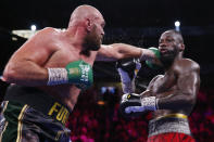 Tyson Fury, of England, hits Deontay Wilder in a heavyweight championship boxing match Saturday, Oct. 9, 2021, in Las Vegas. (AP Photo/Chase Stevens)