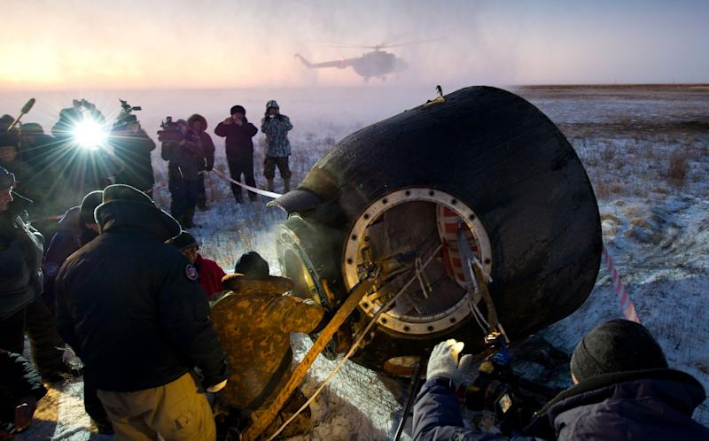 Russian support personnel work to help get Expedition 29 crew members out of the Soyuz TMA-02M spacecraft shortly after the capsule landed with Expedition 29 Commander Mike Fossum, and Flight Engineers Sergei Volkov and Satoshi Furukawa in a remote area outside of the town of Arkalyk, Kazakhstan, on Tuesday, Nov. 22, 2011. NASA Astronaut Fossum, Russian Cosmonaut Volkov and JAXA (Japan Aerospace Exploration Agency) Astronaut Furukawa are returning from more than five months onboard the International Space Station where they served as members of the Expedition 28 and 29 crews. Photo Credit: (NASA/Bill Ingalls)
