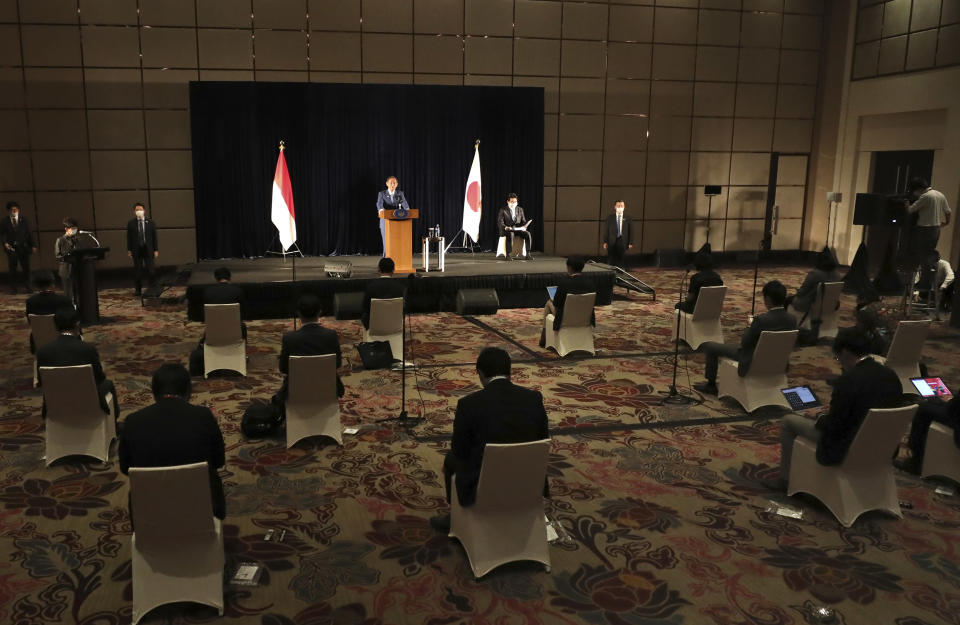 Japanese Prime Minister Yoshihide Suga speaks as members of the media sit spaced apart to maintain physical distancing during a press conference in Jakarta, Indonesia, Wednesday, Oct. 21, 2020. Suga is on a four-day visit to Vietnam and Indonesia. (AP Photo/Dita Alangkara, Pool)