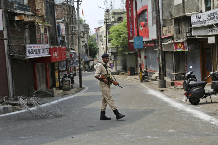 """An Indian paramilitary soldier guards during security lockdown in Jammu, India, Tuesday, Aug.6, 2019. India's lower house of Parliament was set to ratify a bill Tuesday that would downgrade the governance of India-administered, Muslim-majority Kashmir amid an indefinite security lockdown in the disputed Himalayan region. The Hindu nationalist-led government of Prime Minister Narendra Modi moved the """"Jammu and Kashmir Reorganization Bill"""" for a vote by the Lok Sahba a day after the measure was introduced alongside a presidential order dissolving a constitutional provision that gave Kashmiris exclusive, hereditary rights. (AP Photo/Channi Anand)"""