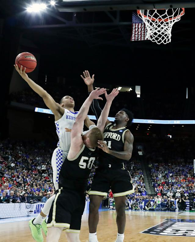 Kentucky's Keldon Johnson, left, shoots over Wofford's Matthew Pegram (50) and Tray Hollowell, right, during the first half of a second-round game in the NCAA mens college basketball tournament in Jacksonville, Fla., Saturday, March 23, 2019. (AP Photo/John Raoux)