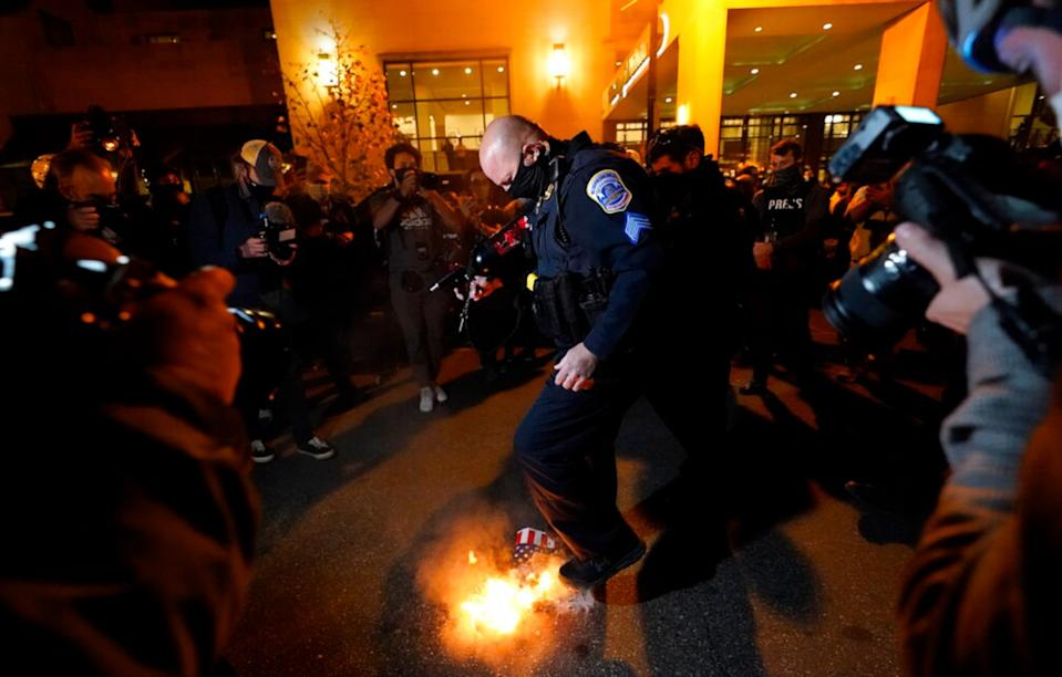 An officer puts out a sign that counter-protesters lit on fire. Source: AP