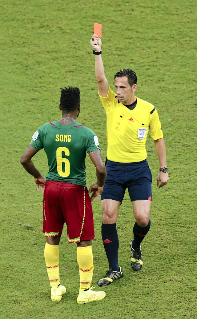 Referee Pedro Proenca from Portugal gives Cameroon's Alex Song (6) a red card, during the group A World Cup soccer match between Cameroon and Croatia at the Arena da Amazonia in Manaus, Brazil, Wednesday, June 18, 2014. Song intentionally struck an opposing player in the back. (AP Photo/Fernando Llano)
