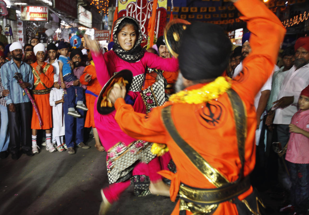 An Indian female Sikh warrior performs the Gatka, a traditional Sikh martial arts, with a male counterpart during a religious procession Khalsa Saajna Divas or Baisakhi festival in Hyderabad, India, Friday, April 13, 2012. Baisakhi is the harvest festival widely celebrated in northern India, especially in the Punjab area. (AP Photo/Mahesh Kumar A.)