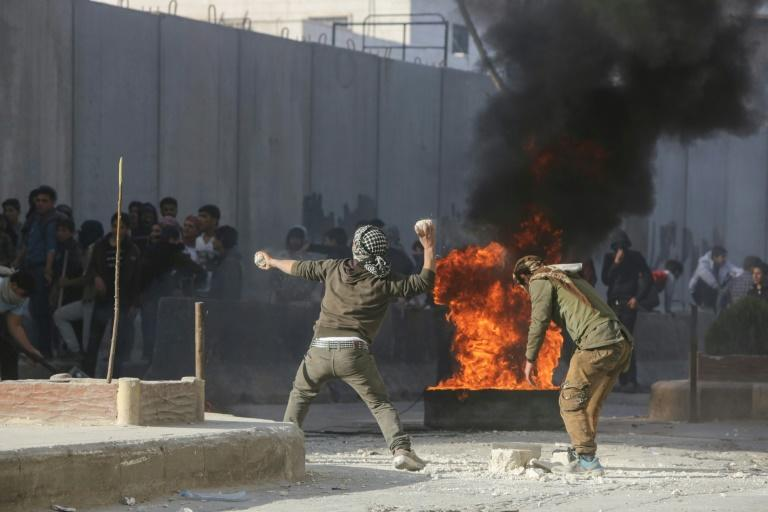 Syrian protesters hurl stones amid clashes with Turkish forces following a demonstration against Turkey's presence in northern Syria on November 17