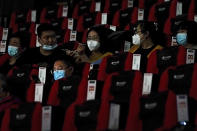 People wearing face masks to help curb the spread of the coronavirus chat each other as the watch a film at Poly Cinema in Beijing on Thursday, Feb. 25, 2021. With coronavirus well under control in China and cinemas running at half capacity, moviegoers are smashing China's box office records, setting a new high mark for ticket sales in February, with domestic productions far outpacing their Hollywood competitors. (AP Photo/Andy Wong)