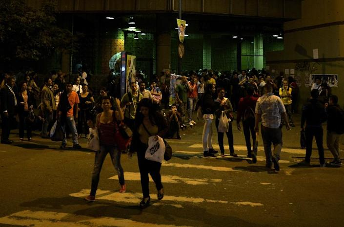 People stand outside a subway station during a general blackout in Caracas (AFP Photo/Juan Barreto)