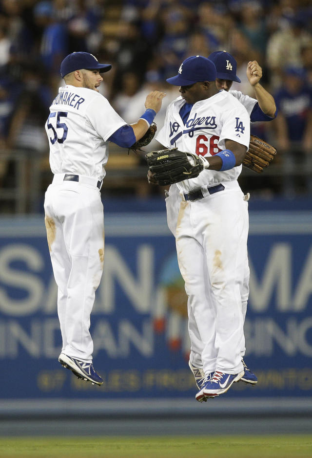 Los Angeles Dodgers' Skip Schumaker(55), Yasiel Puig(66) and Andre Ethier celebrate their team's 2-1 win over the San Diego Padres after an MLB Natioinal League baseball game on Saturday, Aug. 31, 2013, in Los Angeles. (AP Photo/Jae C. Hong)