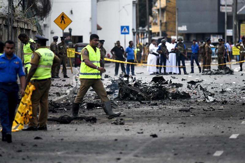 Sri Lankan security personnel inspect the debris of a car after it explodes near St. Anthony's Shrine on Sunday. Source: Getty