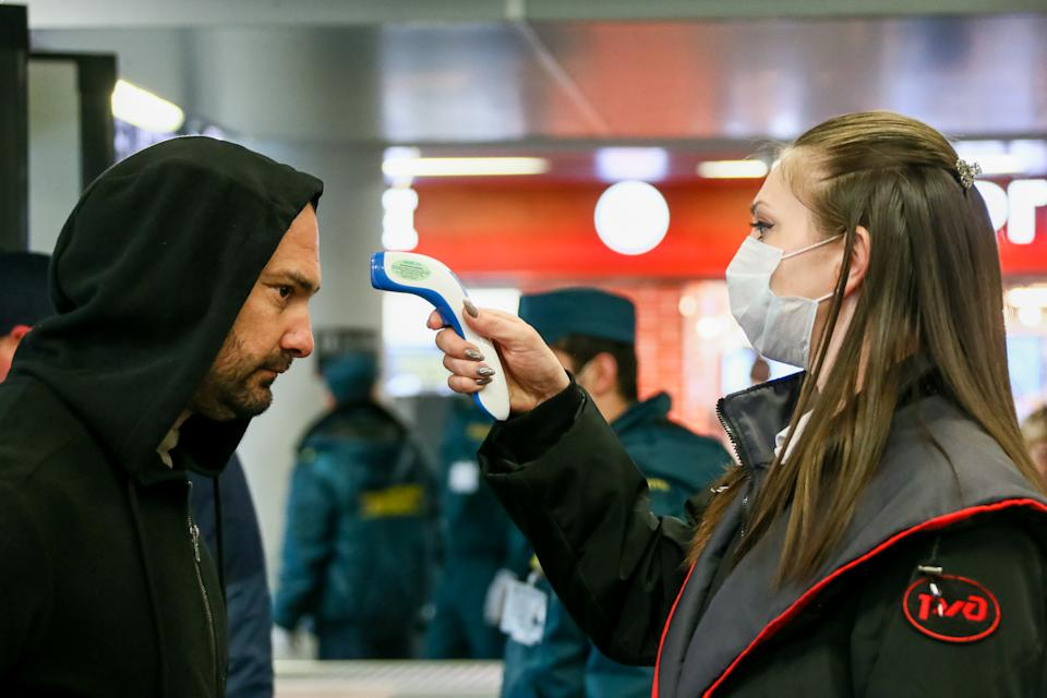 SOCHI, RUSSIA - MARCH 17, 2020: An RZD Russian Railways worker in a face mask scans a passenger's temperature using a digital forehead thermometer at the Adler Railway Station in the Black Sea resort of Sochi during the pandemic of the novel coronavirus (COVID-19). As of 17 March 2020, Russia has confirmed more than 100 cases of the novel coronavirus. Dmitry Feoktistov/TASS (Photo by Dmitry Feoktistov\TASS via Getty Images)