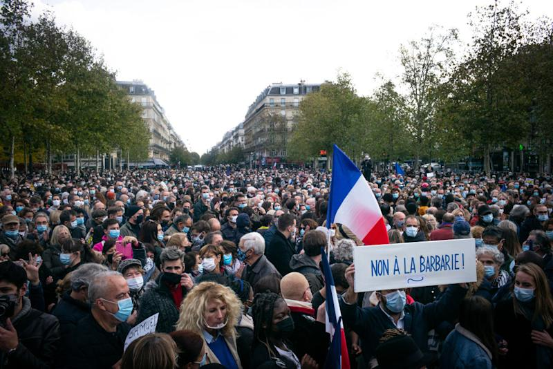A placard saying 'No to Brutality' is seen with thousands of French protesters in the background. Source: Getty