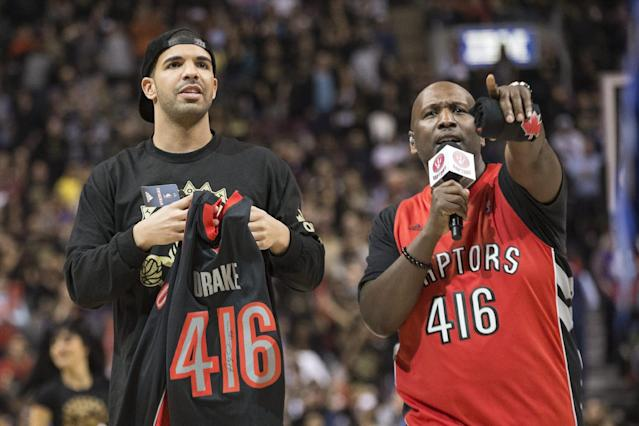 Rapper Drake holds a shirt bearing his name and Toronto's area code during a break in the Toronto Raptors Brooklyn Nets NBA basketball game in Toronto on Saturday Jan. 11 , 2014. (AP Photo/The Canadian Press, Chris Young)