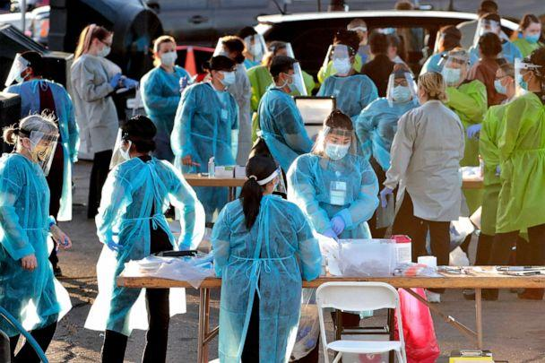 PHOTO: Medical personnel prepare to test hundreds of people lined up in vehicles in Phoenix's western neighborhood of Maryvale in Phoenix for free COVID-19 tests, June 27, 2020. (Matt York/AP, FILE)