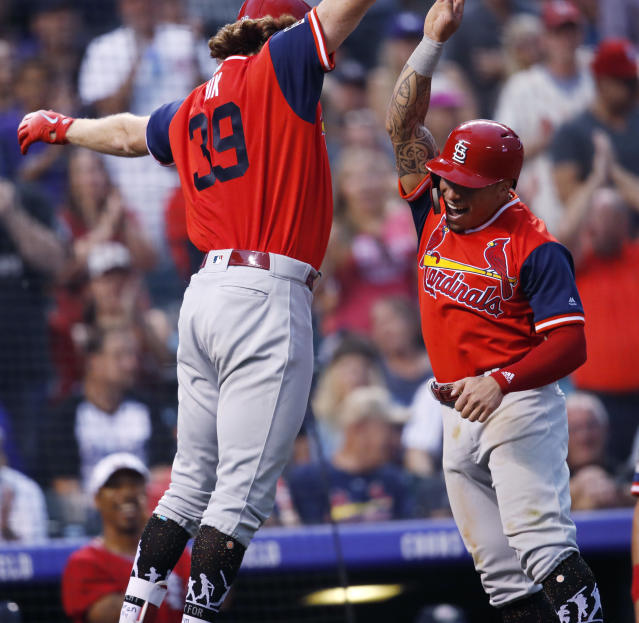 St. Louis Cardinals' Miles Mikolas, left, celebrates with Kolten Wong after Mikolas hit a two-run home run off Colorado Rockies starting pitcher Antonio Senzatela in the second inning of a baseball game Friday, Aug. 24, 2018, in Denver. (AP Photo/David Zalubowski)