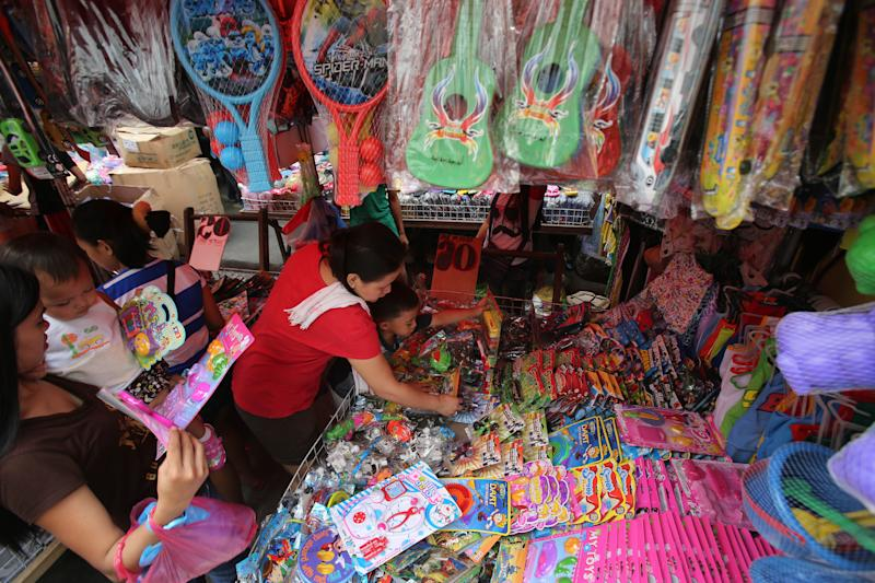 FILE - In this Dec. 23, 2013 file photo, holiday shoppers pick bargain toys at a makeshift store in downtown Manila, Philippines. The Philippine economy expanded 7.2 percent in 2013 despite the havoc wrought in the last months of the year by a super typhoon, an earthquake and a weekslong gun battle that shut down a major port city. Even then, the Philippines was the second best performing economy in Asia after China in the fourth quarter, officials said. (AP Photo/Aaron Favila, File)