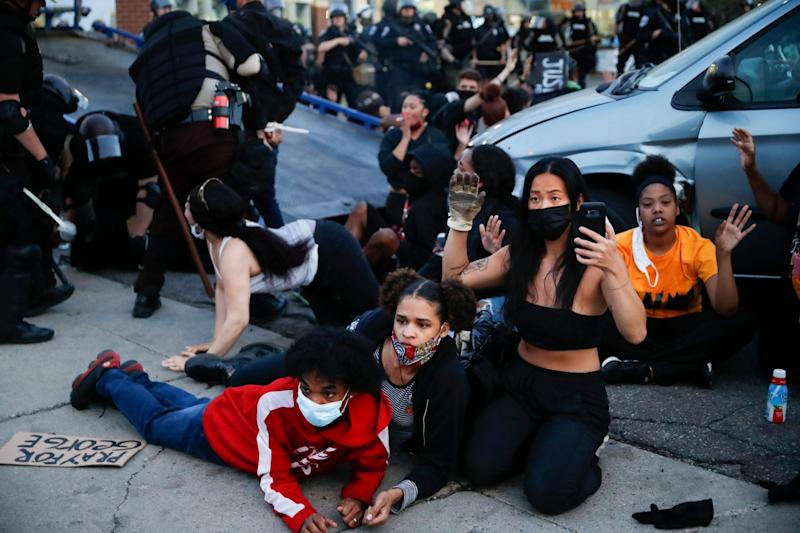 Protesters raise their hands on command from police as they are detained prior to arrest and processing at a gas station on South Washington Street in Minneapolis: AP