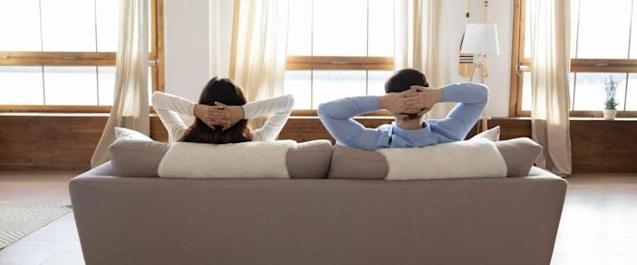 Rear view full length young couple relaxing on couch in modern home — not refinancing their mortgage.