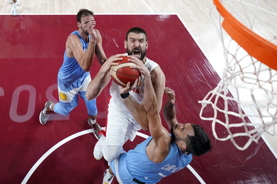 Spain's Marc Gasol, center, drives to the basket against Argentina's Facundo Campazzo (7) during a men's basketball preliminary round game at the 2020 Summer Olympics, Thursday, July 29, 2021, in Saitama, Japan. (AP Photo/Eric Gay)