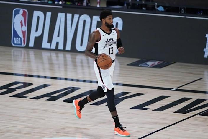 """Clippers forward Paul George brings the ball up court against the Mavericks during Game 5 of their playoff series on Tuesday. <span class=""""copyright"""">(AP)</span>"""