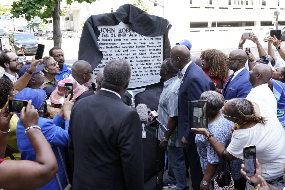 People watch as a new historical marker remembering former Rep. John Lewis is unveiled Friday, July 16, 2021, in Nashville, Tenn. Earlier this year, Nashville's Metro Council renamed a large portion of Fifth Avenue to Rep. John Lewis Way. (AP Photo/Mark Humphrey)