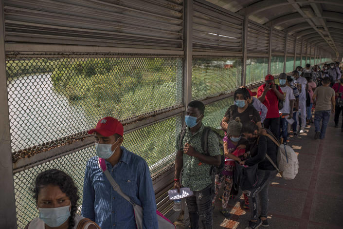 Migrants, mostly from Central America and Haiti, wait on the International Bridge to enter the United States to seek asylum, in Matamoros, Mexico, Aug. 23, 2021. (Daniele Volpe/The New York Times).