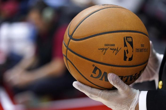 """<span class=""""caption"""">A security guard wears gloves while holding a basketball during halftime of an NBA game in Houston on March 5, 2020. The NBA has told players to avoid high-fiving fans and to avoid taking any item for autographs. </span> <span class=""""attribution""""><a class=""""link rapid-noclick-resp"""" href=""""http://www.apimages.com/metadata/Index/Clippers-Rockets-Basketball/8ce561fb32c145cebef58687fe446558/56/0"""" rel=""""nofollow noopener"""" target=""""_blank"""" data-ylk=""""slk:AP Photo/David J. Phillip"""">AP Photo/David J. Phillip</a></span>"""
