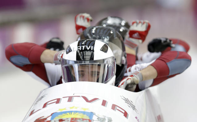 The team from Latvia LAT-2, with Oskars Kibermanis, Raivis Broks, Helvijs Lusis and Vairis Leiboms, start their third run during the men's four-man bobsled competition final at the 2014 Winter Olympics, Sunday, Feb. 23, 2014, in Krasnaya Polyana, Russia. (AP Photo/Natacha Pisarenko)