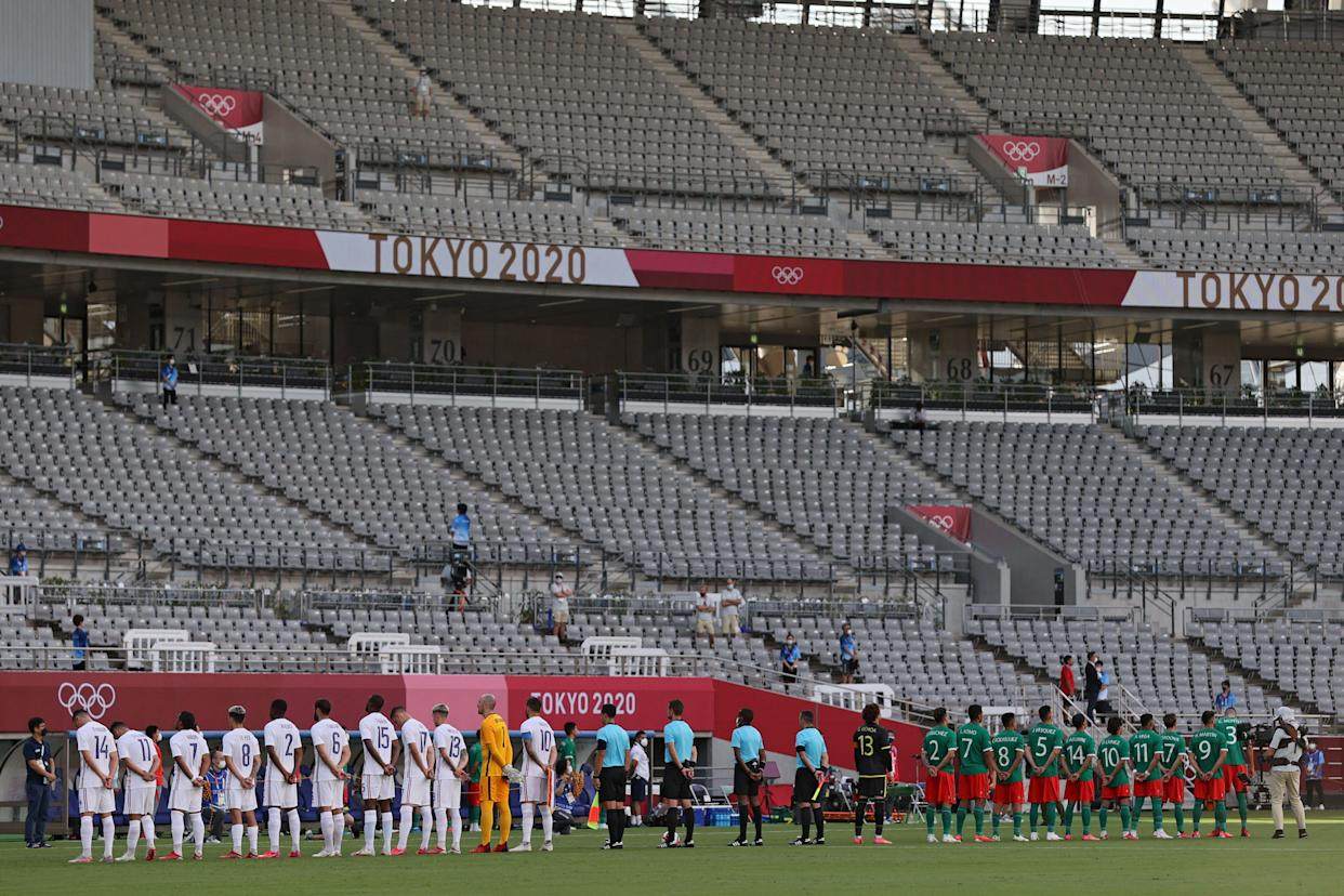 Players gather on the pitch ahead of the Tokyo 2020 Olympic Games men's group A first round football match between Japan and South Africa at Tokyo Stadium in Tokyo on July 22, 2021. (Photo by Mariko Ishizuka / AFP) (Photo by MARIKO ISHIZUKA/AFP via Getty Images)