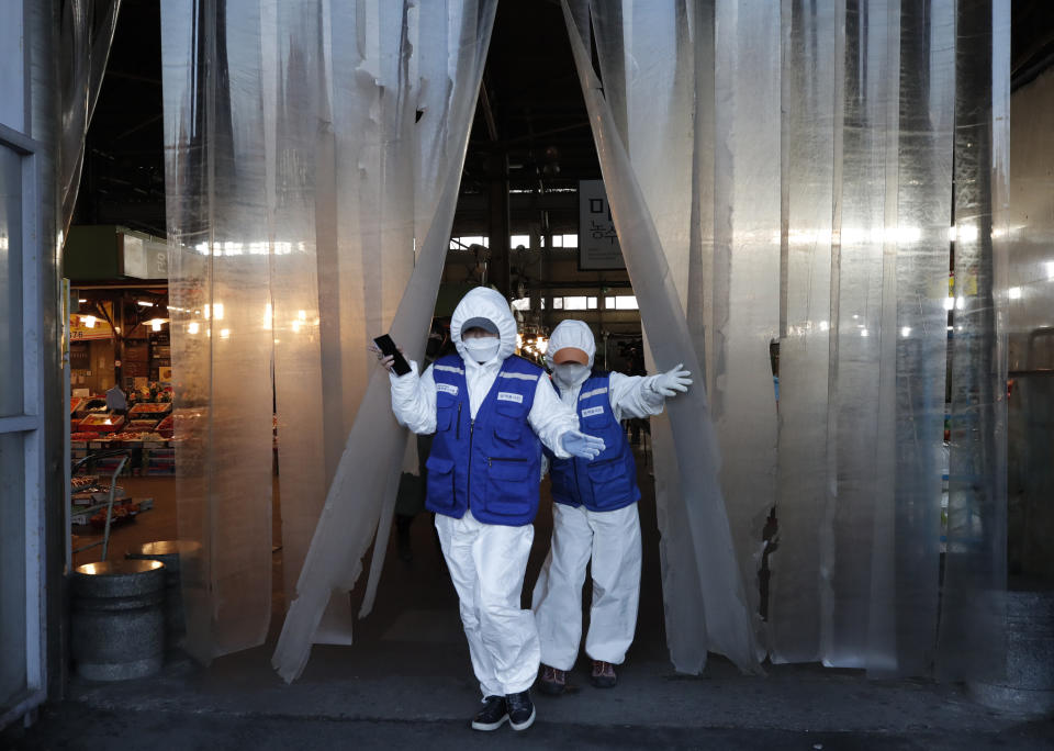 Workers wearing protective suits walk before they spray disinfectant as a precaution against the COVID-19 at a market in Seoul, South Korea, Thursday, Feb. 27, 2020. The new illness persists in the worst-hit areas and spreads beyond borders. (AP Photo/Lee Jin-man)