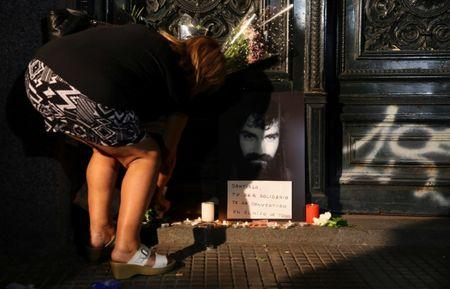 A woman places flowers next to a portrait of Santiago Maldonado, a protester who went missing since security forces clashed with indigenous activists in Patagonia on August 1, 2017, at the entrance of a judicial morgue in Buenos Aires, Argentina October 20, 2017.  REUTERS/Marcos Brindicci