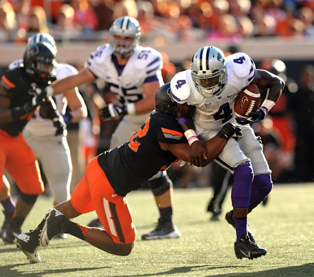 Oklahoma State linebacker Ryan Simmons, left, tackles Kansas State quarterback Daniel Sams, right, during the second half of an NCAA football game in Stillwater, Okla., Saturday, Oct. 5, 2013. Oklahoma State won 33-29. (AP Photo/Brody Schmidt)