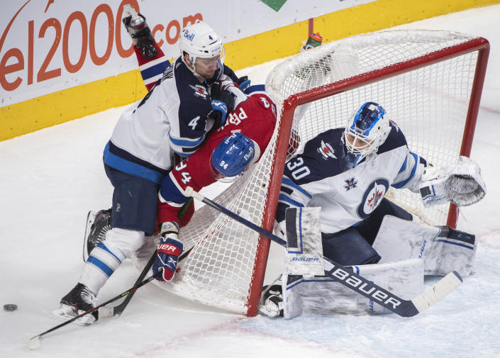 Winnipeg Jets goaltender Laurent Brossoit looks on as Jets' Neal Pionk (4) upends Montreal Canadiens' Corey Perry (94) during the third period of an NHL hockey game Saturday, March 6, 2021, in Montreal. (Graham Hughes/The Canadian Press vIa AP)